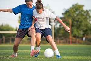 NC Surgery Lifestyle Image Female Kicking Soccer Ball