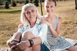 Mother confidently sitting in park with daughter wearing shorts