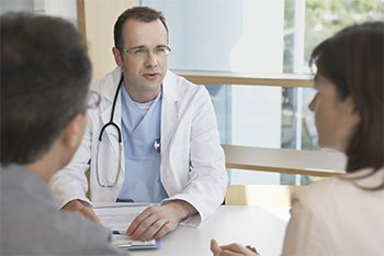 Couple talking over decisions with doctor